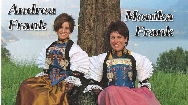 Andrea und Monika Frank im Trachtengewand, an einen Baum lehnend. Im Hintergrund ein See.