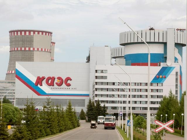 Zu sehen ist ein russisches Atomkraftwerk mit zwei  Kühltürmen. Davor stehen drei Personenwagen und das Werk ist mit kyrillischer Schrift bemalt.