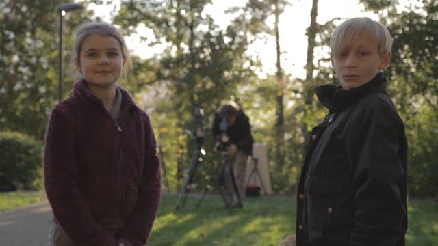 Die beiden Kinder sind frontal zu sehen, im Hintergrund bedient ein Kameramann eine Kamera.