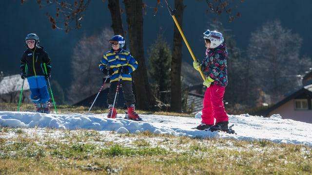 Kinder am Skilift auf einem Schneestreifen mitten in der grünen Wiese.