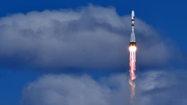 La racheta dal tip Sojus davant in fund blau cun nivels grischs.