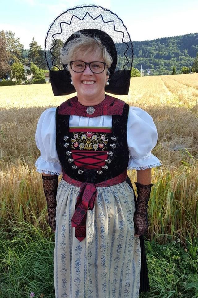 Eine strahlende Frau in einer Tracht am Rand eines Felds.