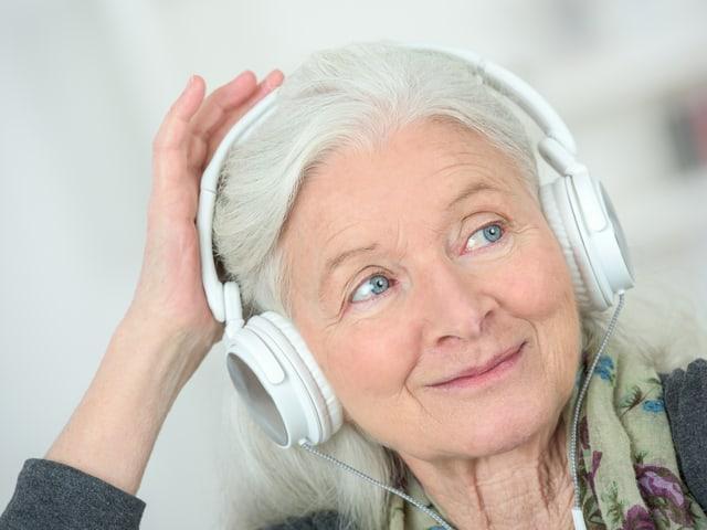 Seniorin mit Kopfhörer.
