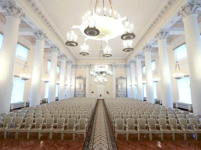 Der weisse Ballsaal vom Smolny-Institut: Weisse Stühle sind symmetrisch angeordnet, in der Mitte liegt ein langer Teppich, der bis zur Türe reicht.