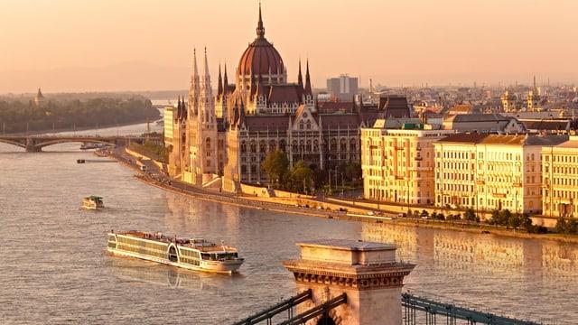 Ein Schiff auf einem Fluss vor einem Palast.