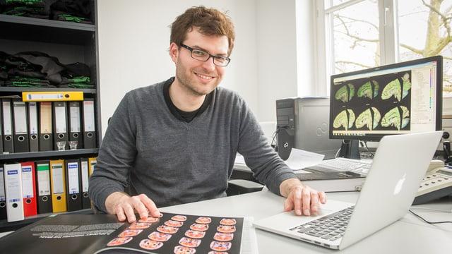 Sebastian Markett hinter seinem Schreibtisch mit Buch und Laptop.