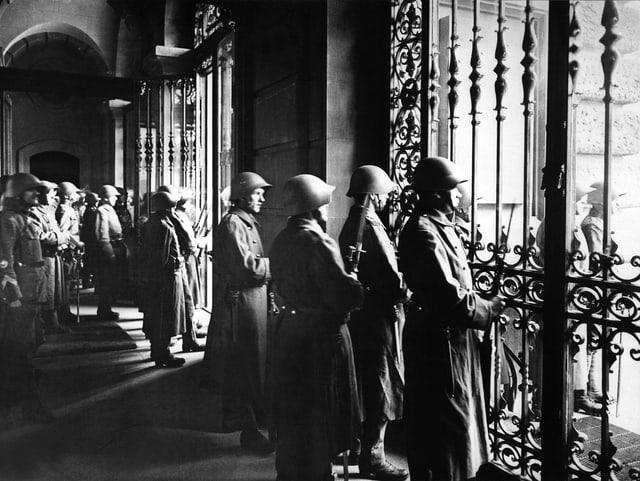 Soldaten schauen durch Fensterscheiben des Bundeshauses hinaus ins Freie.