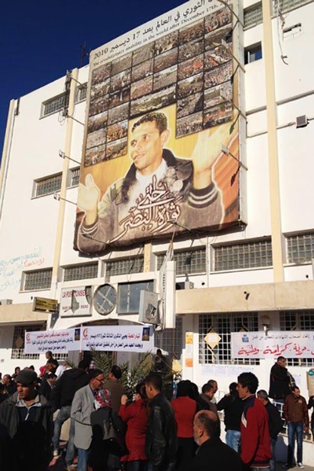 An einer Häuserwand ein grosses Plakat mit einem jungen Mann.