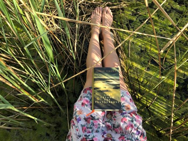 Der Roman «Der Geang der Flusskrebse» von Delia Owens liegt auf Annette Königs Beinen