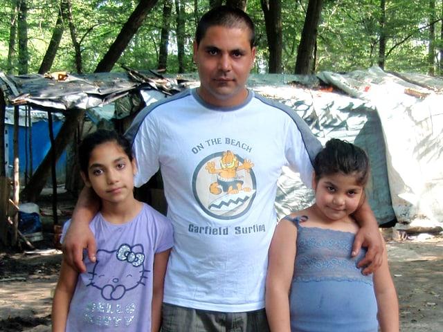 Mann mit seinen beiden Töchtern im Slum.