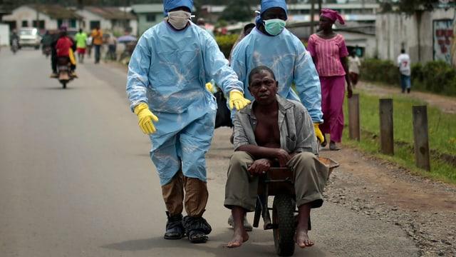 Ebola-Erkrankter wird Leuten in Schutzkleidung in einer Schubkarre transportiert