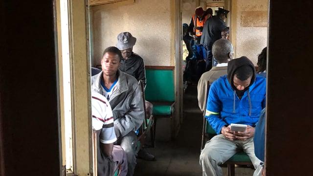 Blick in den Zugwaggon: Die Männer sitzen und starren in ihr Smartphone.