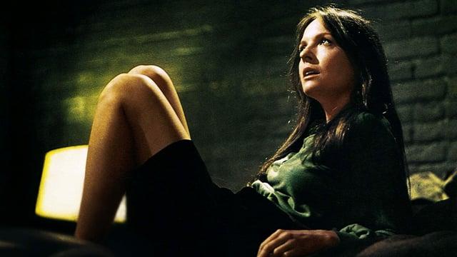 Eine Frau mit langen braunen Haaren sitzt auf dem Bett. Ihre Beine sin angezogen und sie stützt sich auf den Ellbogen ab. Sie trägt einen schwarzen Minirock und schaut mit leicht geöffnetem Mund zur Decke.