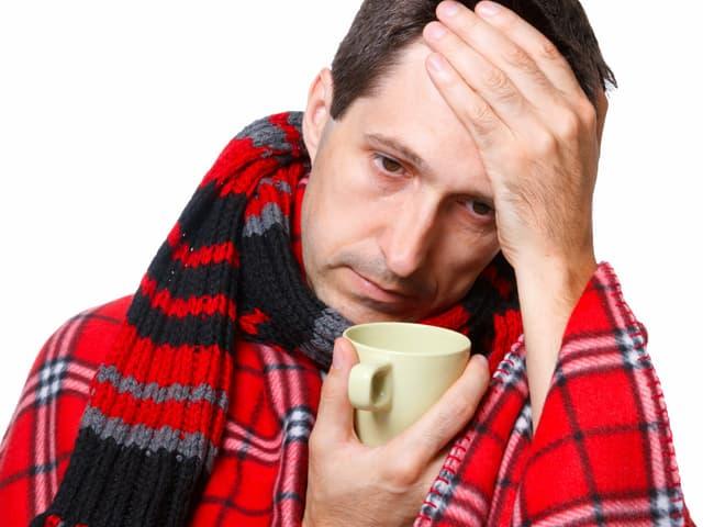 Ein Mann mit Grippe und einer Tasse Tee.