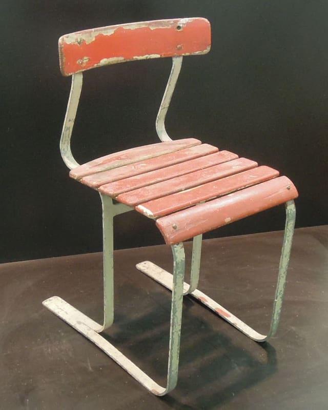 Einfacher Stuhl aus Metall und rot lackierten Holzlatten.