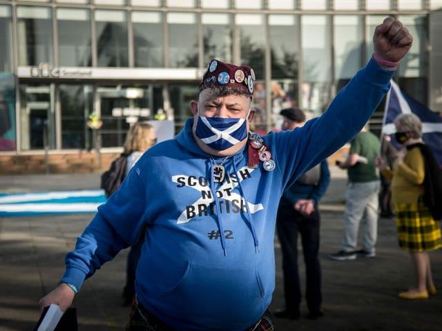 Schotte mit blau-weissem Pulli und entsprechendem Mundschutz.