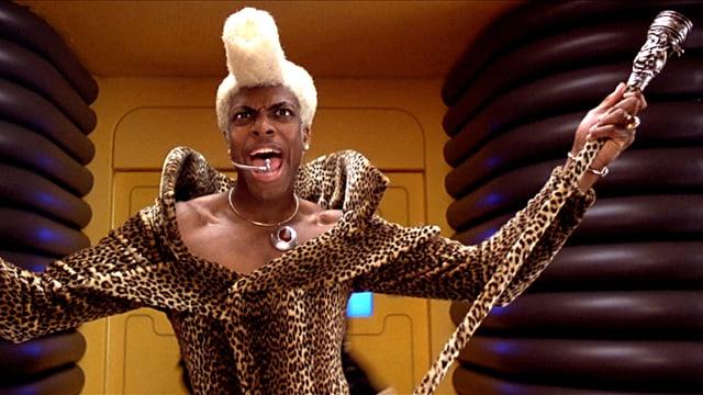 Ein Mann im Leoparden-Outfit und Turmfrisur.