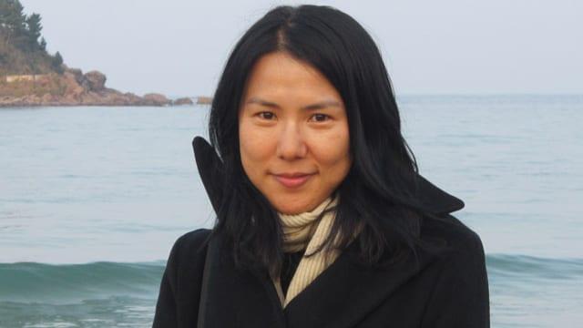 Porträt von Suki Kim mit beigem Schal um den Hals.