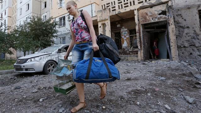 Eine Frau verlässt mit Taschen und einem Vogelkäfig ein zerstörtes Wohnhaus.