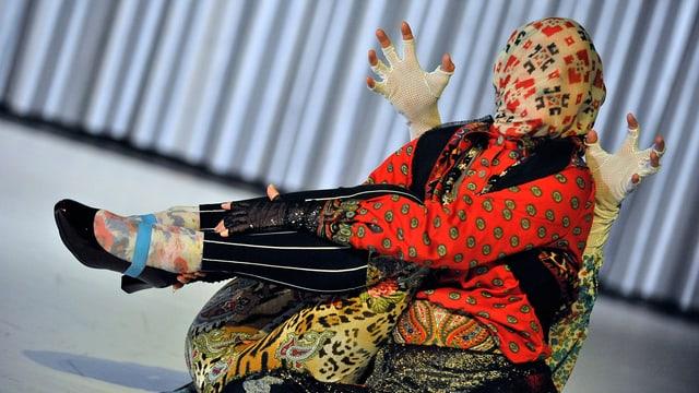 Zwei mit farbigen Stoffen total vermummte Figuren, dicht hintereinander und quasi verschmelzend auf der Bühne.