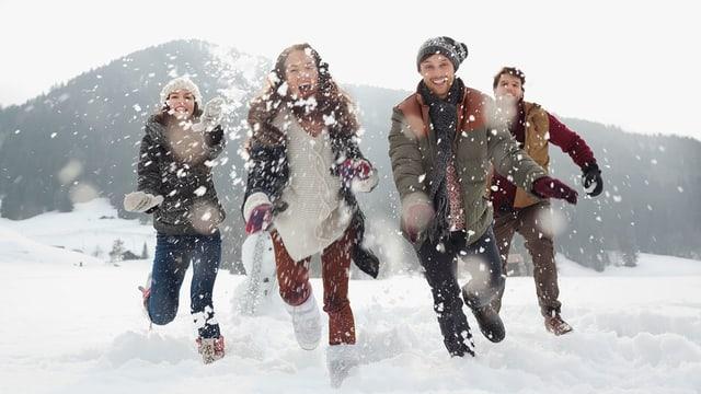 Junge Menschen rennen durch den Schnee.