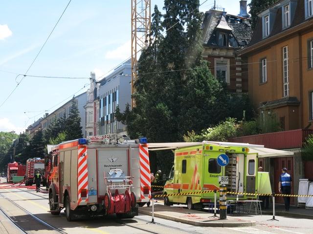 Ein Feuerwehrauto im Vordergrund, zwei weitere im Hintergrund. Dazu ein Sanitätsfahrzeug. Alles vor dem ausgebrannten Haus