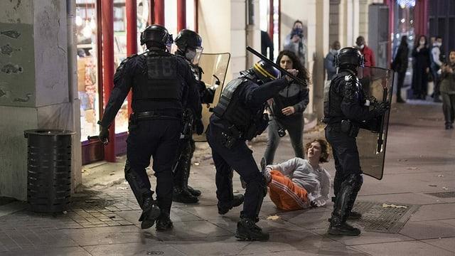 Vier Polizisten stehen auf der Strasse, einer verprügelt mit einem Schlagstock eine Passantin.