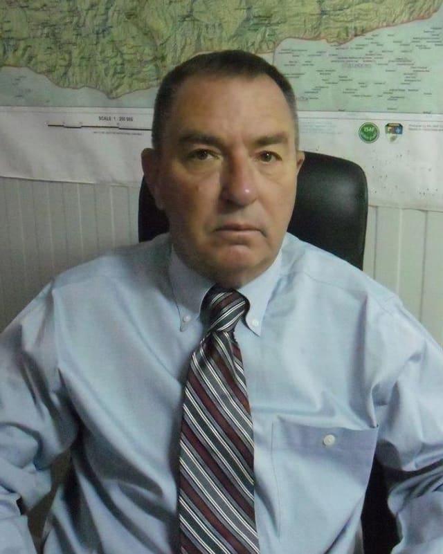 Der Militarstratege Gary Anderson in Hemd und Krawatte sitzend vor einer Landkarte an der Wand.