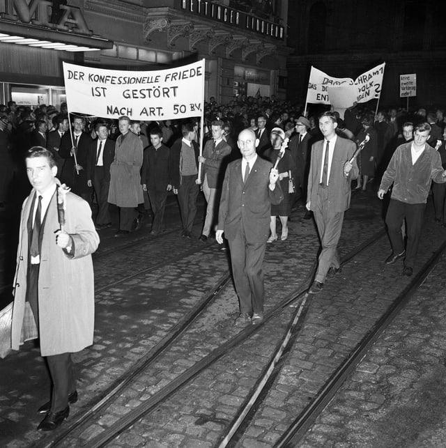 Junge Christen demonstrieren 1963 in Basel mit Fackeln und Transparenten.