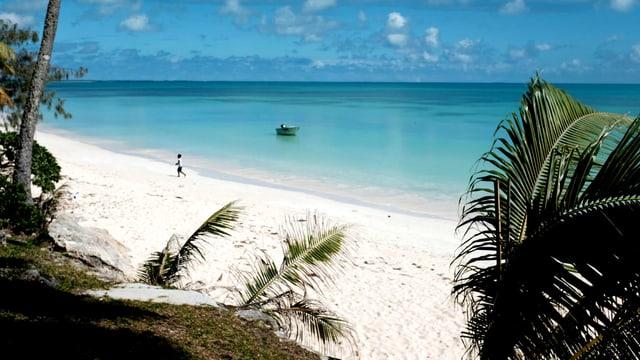 Ein weisser Strand, an dem ein kleiner Junge entlangläuft.