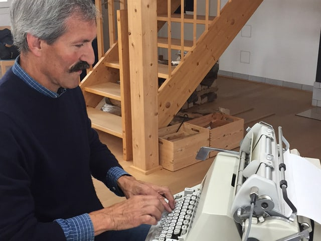 Ein Mann im blauen Pullover sitzt vor einer weissen Schreibmaschine und tippt.