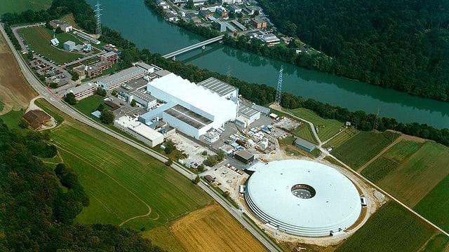 Aufnahme aus der Luft vom Paul Scherrer Institut. Zu sehen ist ein grosses rundes, flaches Gebäude. Daneben ein hohes, industrieartiges weisses Gebäude. Rund um die Anlage hat es Ackerland.