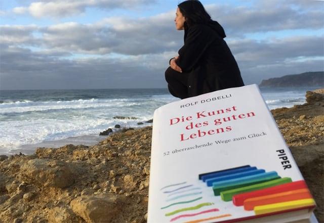 Frau blickt aufs Meer.