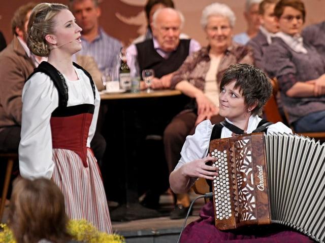 Barbara Klossner schaut nach oben und singt und Andrea Ulrich schaut zu Barbara Klossner und spielt Akkordeon.