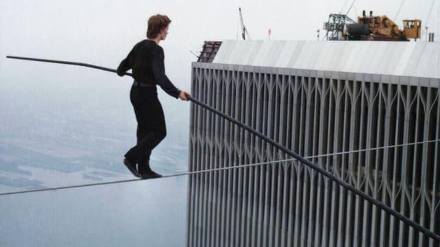 Ein Mann geht auf einem Seil zwischen zwei Hochhäusern. In seinen Händen hält er eine Balancierstange.