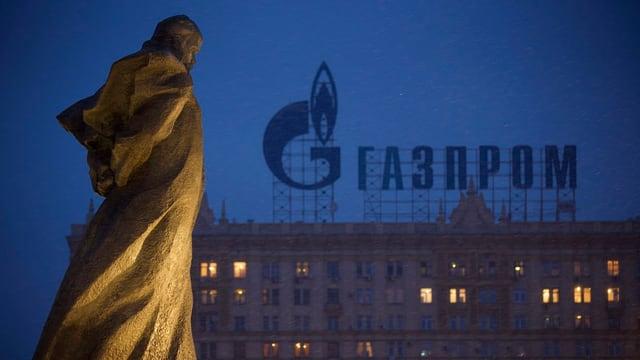 Schriftzug des russischen Gasanbieters Gazprom auf einem Gebäude in Moskau, links vorne eine Statue des Schriftstellers Taras Schewtschenko.