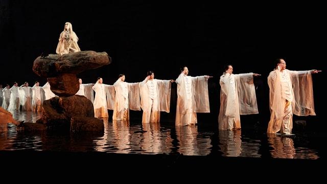 Mehrere Personen laufen hintereinander durch eine Wasserfläche. Alle haben lange Gewänder. Auf einem Steinturn sitzt eine Frau.