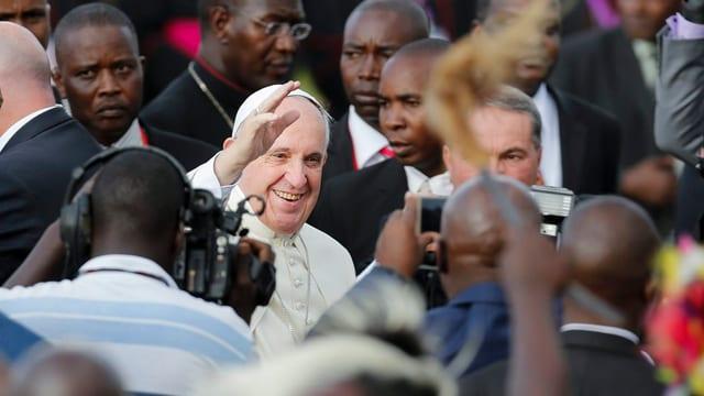 Der Papst umringt von einer Menschenmenge.