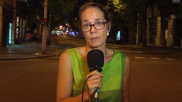 Frau spricht in ein Mikrofon, sie steht des Nachts auf einer Strasse.