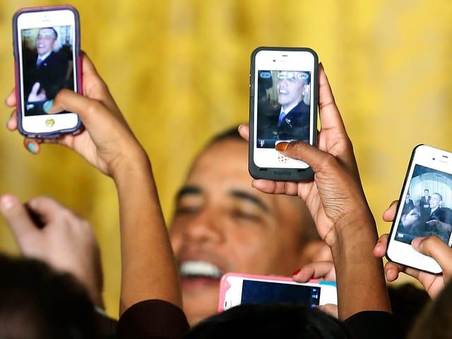 Obama wird von Menschen mit Smartphone gefilmt.