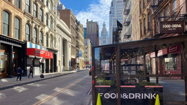 Eine leere Strasse in New York mit hohen Gebäuden und einem Essensstand