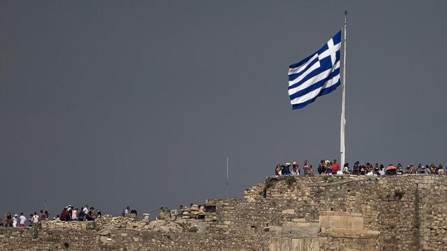 Symbolbild: Griechische Flagge aus der Ferne flattert im Wind, darunter Menschen.
