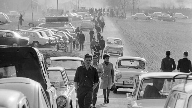 Eine Grosse Zahl von Autos steht auf einem Feld parkiert, gleich neben einer Strasse. Dort laufen viele Personen entlang.