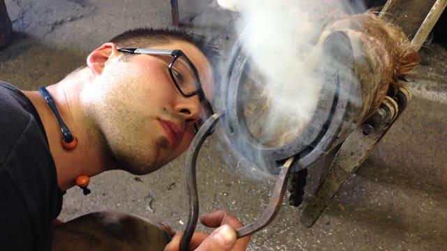 Lehrling kniet und begutachtet das rauchende Eisen.