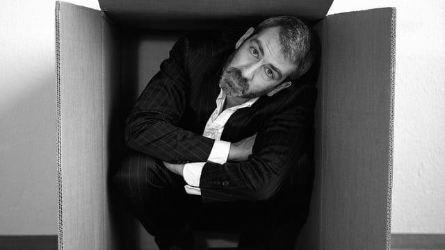 Der Kabarettist Manuel Stahlberger kauert in einer Kartonschachtel, in der er kaum Platz hat.