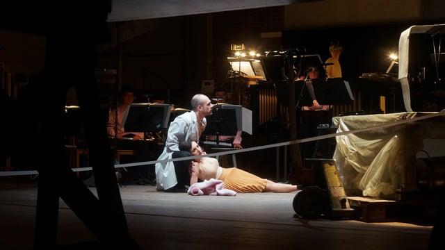 Theaterszene, Ein Mann kniet am Boden und hält eine liegende Frau.