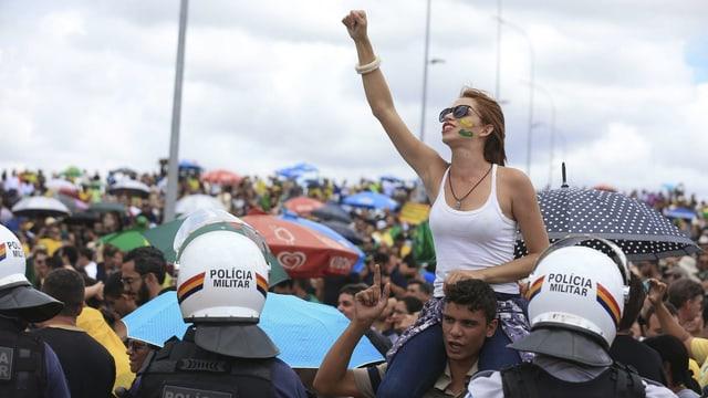 Demonstration, eine junge Frau sitzt auf den Schultern eines Mannes und reckt die Faust in die Höhe, vor Ihr Polizisten in Helm und Kampfmontur.