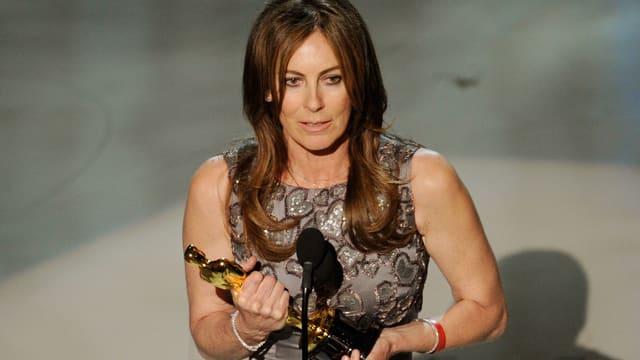 Kathryn Bigelow im Abendkleid, hält den Oscar.