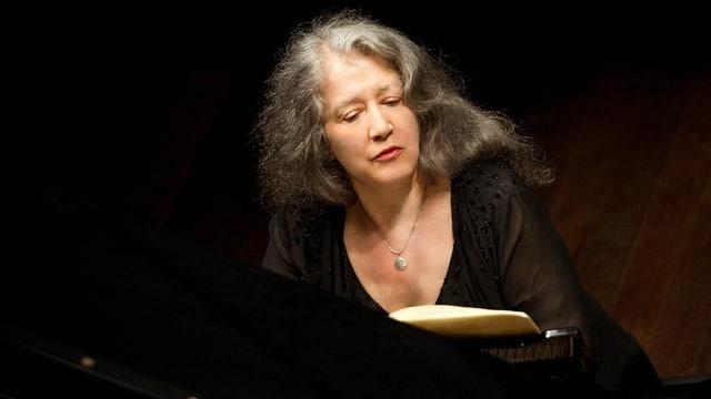 Ein ältere Frau mit schwarzem Kleid an einem Klavier.