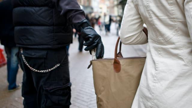 Ein Mann mit Handschuhen greift in die offene Umhängetasche einer Frau.